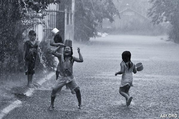 trẻ con tắm mưa