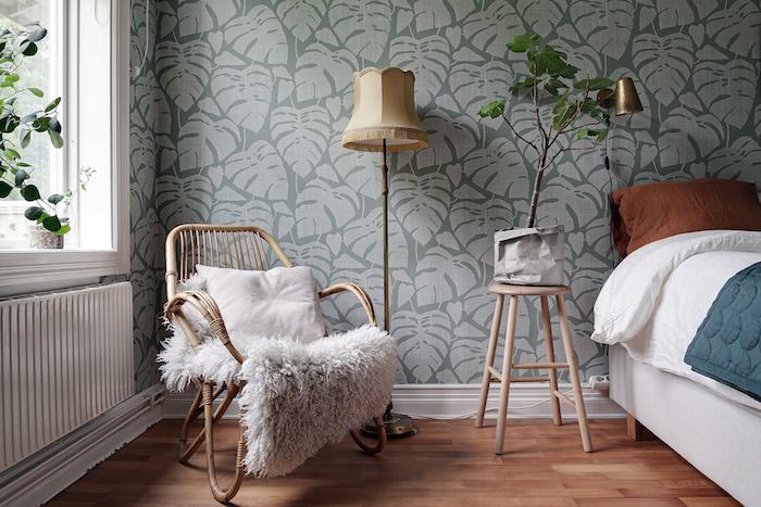 Dormitorio con cabecero forrado con papel pintado a media altura y muebles antiguos reciclados