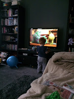 Child standing in front of the TV watching the movie