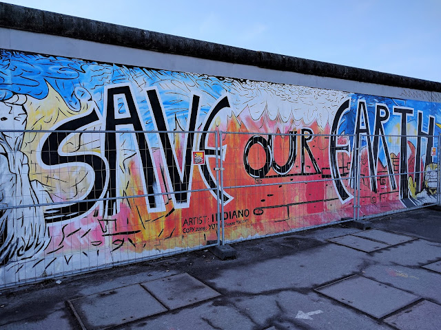 "East Side Gallery - painted wall saying ""save the earth"""