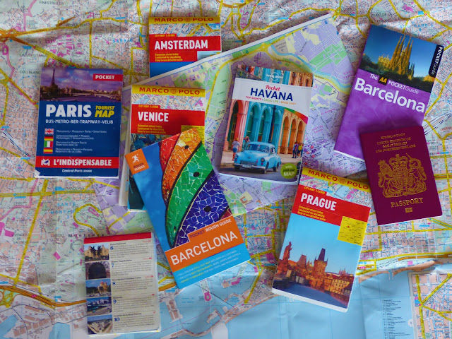 A flatlay of a map, plus travel maps and guidebooks for Paris, Barcelona, Prague, Marrakech, Havana and Venice