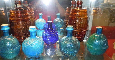 Half a dozen patterned glass balls with necks like a wine or beer bottle's neck. They are various shades of blue. The photo is taken in front of a reflective surface, with the camera's flash visible at the top.