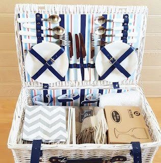 An open white picnic basket full of cutlery, plates and blue and white linens