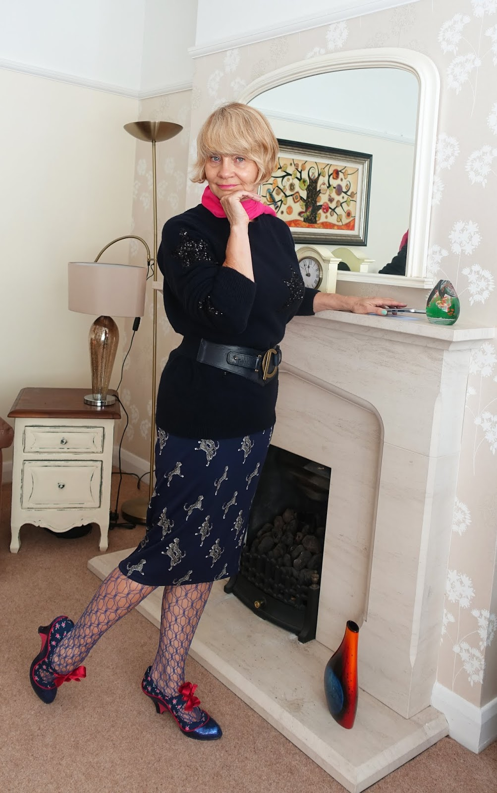 Fancy tights and shoes and a pink scarf add some sizzle to a patterned blue skirt and sequinned navy blue jumper