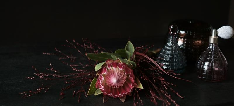 Blog + Fotografie by it's me! - Protea mit roten Gräsern und Glasflakons