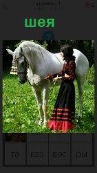 стоит белый конь с изогнутой шеей и рядом девушка в длинной юбке