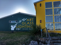 bright blue and yellow building with silhouette of a glass blower and the words art, glass, and lighting