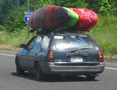 Small stationwagon with 4 kayaks tied to the top luggage rack