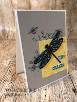This image shows a hand made card with a black die cut dragonfly hovering over some Designer Series Paper by Stampin' Up!