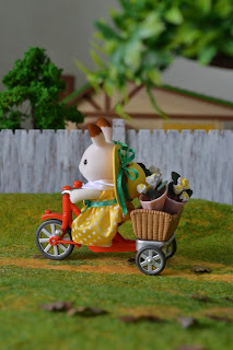 Sylvanian Families Stella rabbit in village riding bike with flowers