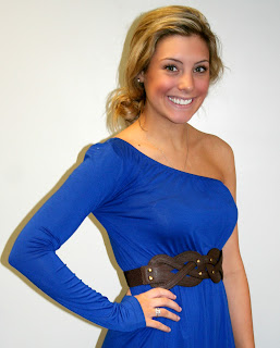 A model poses in a 'One Long Sleeve' blue dress by A Cut Above, featuring a long sleeve on the right arm and no sleeve or shoulder on the left arm.