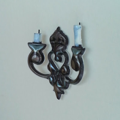 One-twelfth scale metal wall candle holder with white candles.