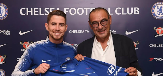 Chelsea and Sarri hold up chelsea jersey after signing for the premier league club
