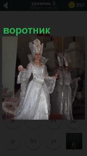 Женщина в белом платье с высоким воротником, похожа на снежную королеву