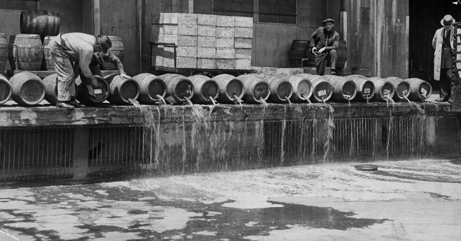 At an army base in Brooklyn, men drain 10,000 barrels of beer into New York Harbor.