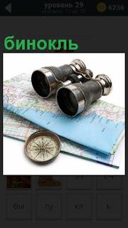 Свернутая карта с компасом и бинокль сверху положен. Можно отправляться в путешествие