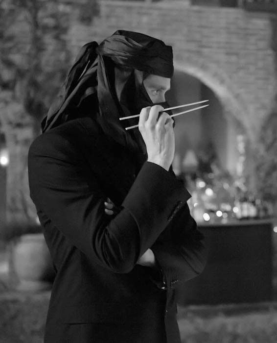 Alexis Denisof in profile, wearing dinner jacket and head draped in black ninja-style, holding chopsticks