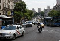 En primer plano un taxi actual, blanco con franja roja cruzando la puerta de delantera, circulando por la calle.