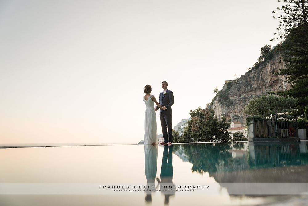Bride and groom reflection in Hotel Convento's infinity pool