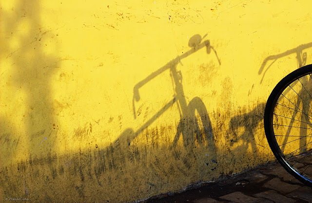 A Minimalist Photo of Shadow of a bicycle on a yellow Indian wall.