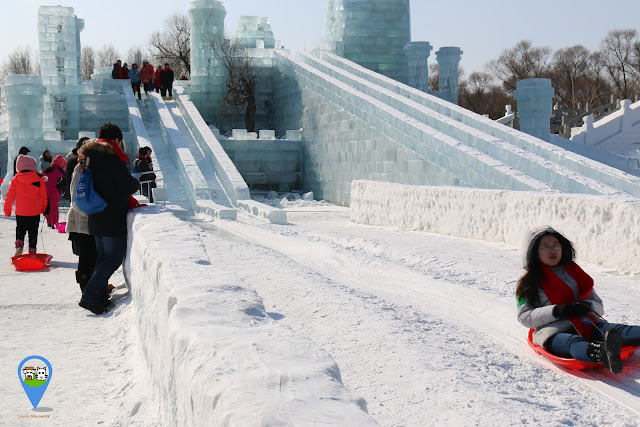 Enjoying the slide on ice sculpture in very cold winter at Harbin Snow Sculpture Art Expo in Heilongjiang province, China