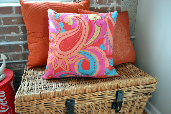 Basket Bench with colorful orange pillows