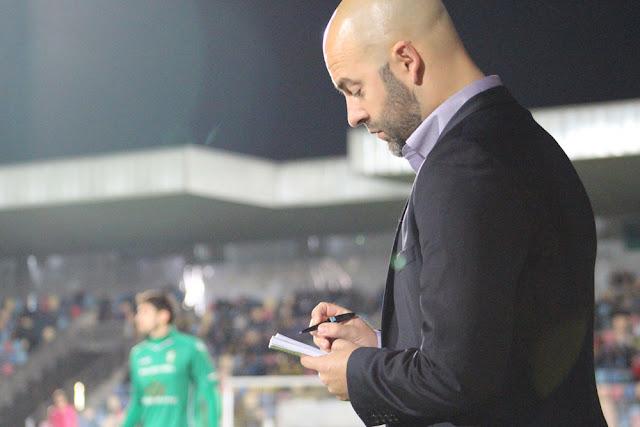Movilla toma notas en su cuaderno durante el partido