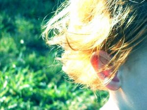 Red hair reflecting in the sunlight in front of green grass. Stock Photo credit: samplediz