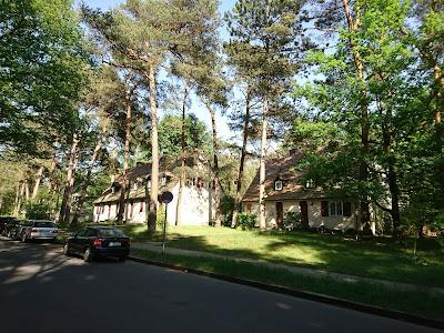 Blick entlang der Straße in der Wohnsiedlung Krumme Lanke. Ein kitschiges Holzartiges Haus steht unter Nadelbäumen.