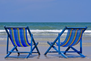 Image of two lounge chairs on the beach.