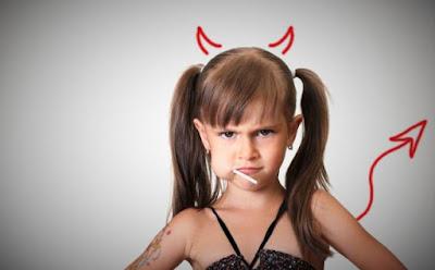 بهذه التصرفات تُشجّعين طفلكِ على سوء السلوك طفلة شقية شيطانة تلبس شيطان تأكل حلوى girl little eating candy satan devil wear naughty miss behave