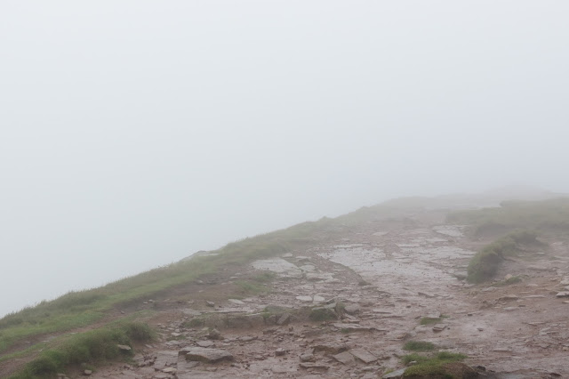 A stone path leading through mist to a barely discernible cairn that marks the summit.