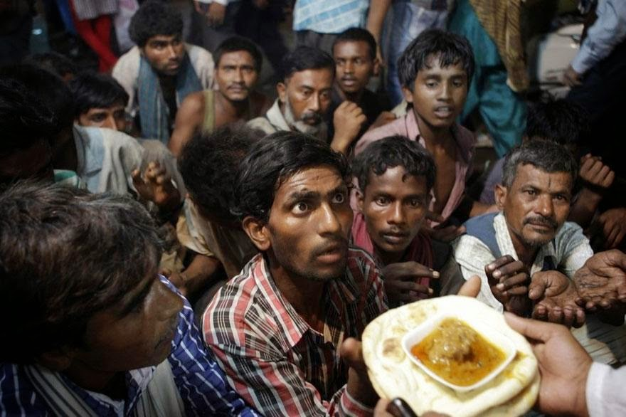 30 of the most powerful images ever - Indian homeless men wait to receive free food distributed outside a mosque ahead of Eid al-Fitr in New Delhi, India