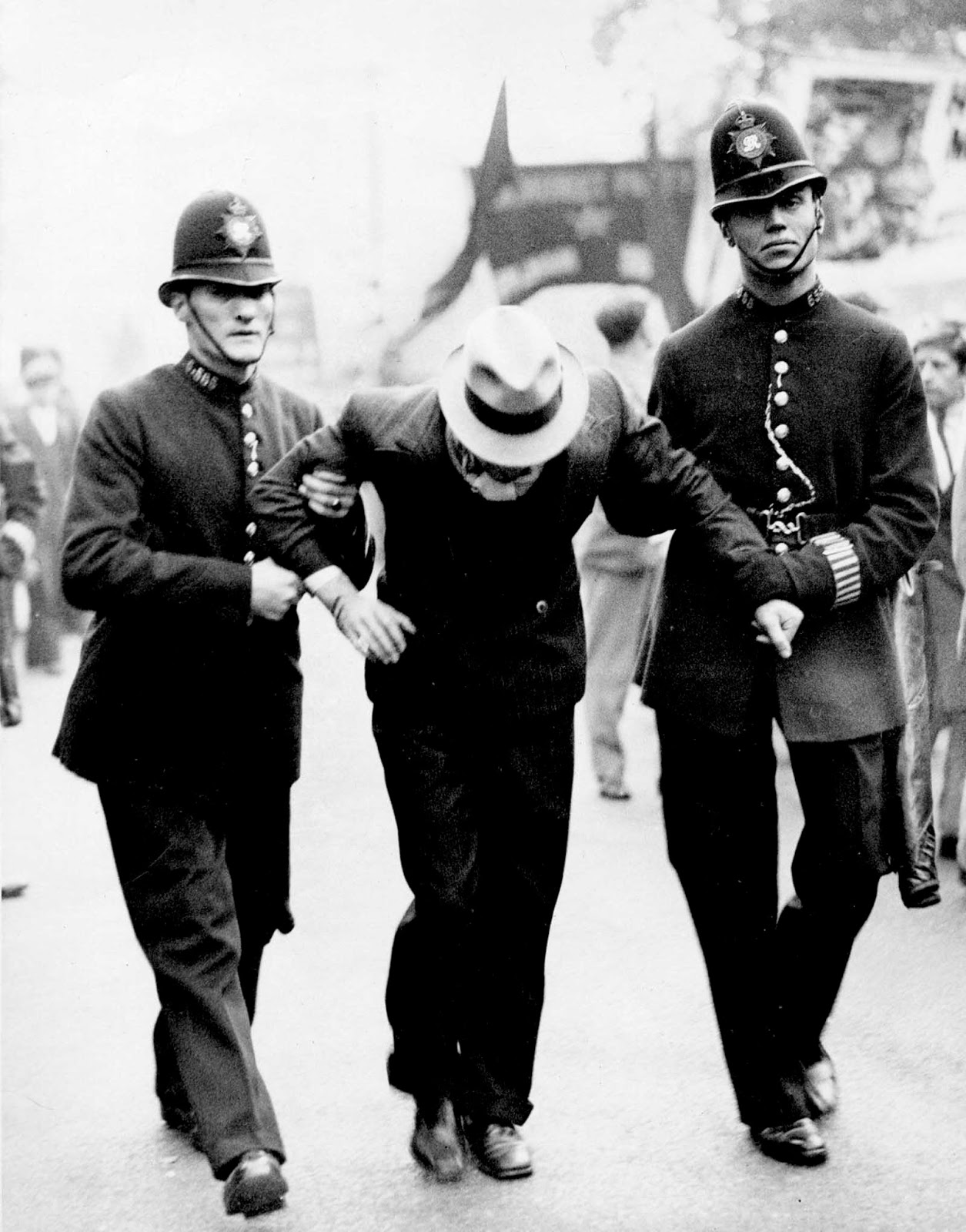 A participant at the 'Communists' March' from Tower Hill to Victoria Park in London, is marched away by police after being arrested. 1936.