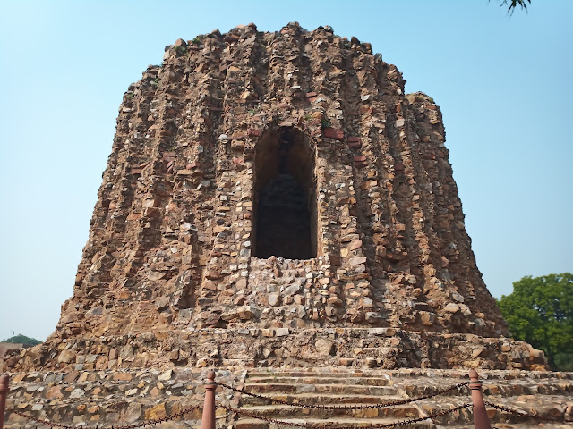 Unfinished wide tower base of rough stone with arched window in Qutub complex, Delhi