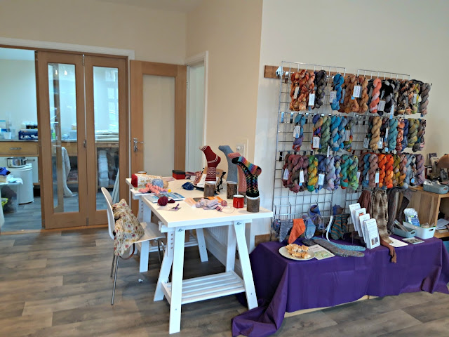 Display table set up with socks from the new More Super Socks book by Winwick Mum.  To the right of the photo are more skeins of hand-dyed yarn on wall racks.
