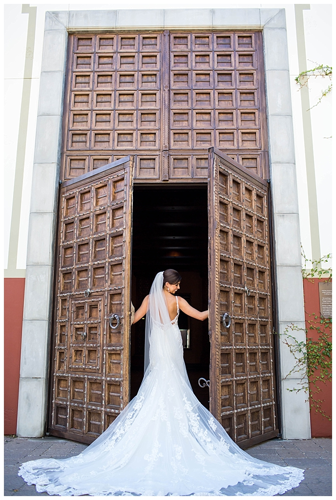 beautiful elegant bride in front of big wood doors at Omni Montelucia