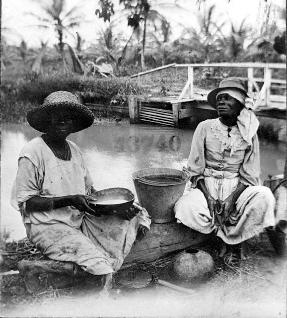 Two women with buckets seated at a stream of water or river. Bridge visible. 1922. Guyana, South America