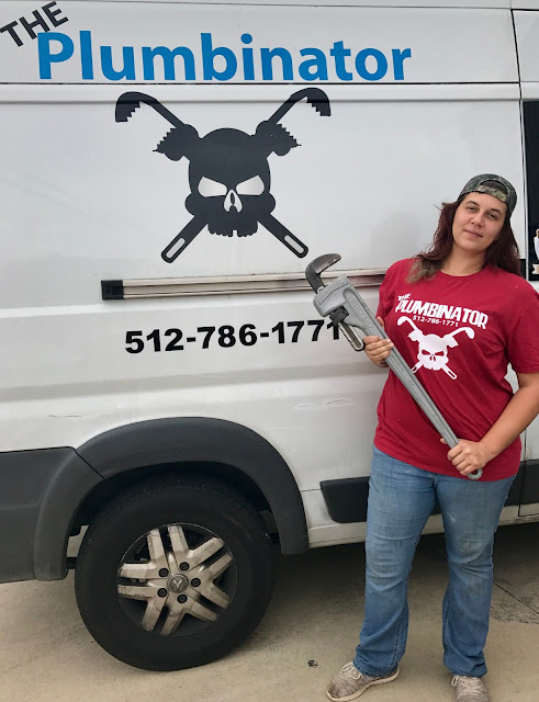 A medium-build brown haired white woman in her 20s holding a four foot long plumbing wrench stands, smiling, by a white van with The Plumbinator logo