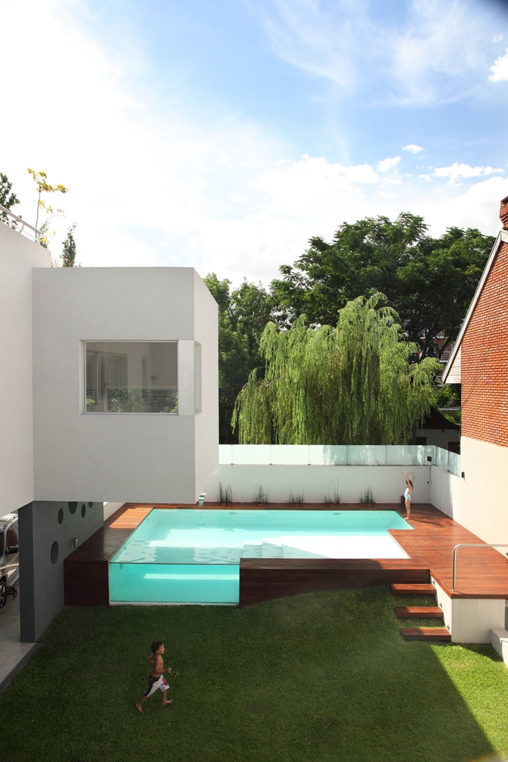 Kids in the backyard of Modern Villa Devoto by Andres Remy Architects