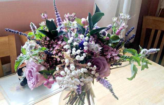 |A variety of pastel-coloured flowers, including mauve roses, arranged in a vase