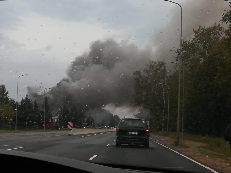 Melni dūmi ceļas no ugunsgrēka blakus šosejai