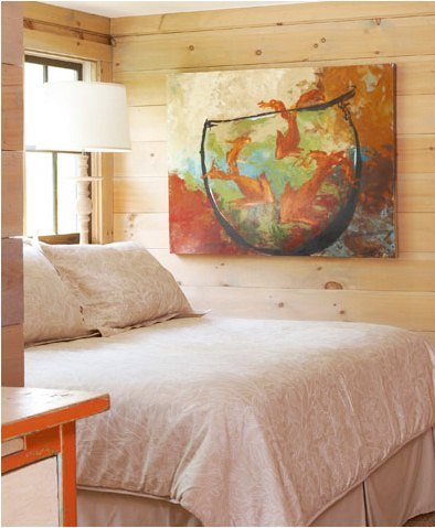 Cozy bedroom with knotty light colored wood paneled walls with a large piece of modern art depicting three fish in a fishbowl