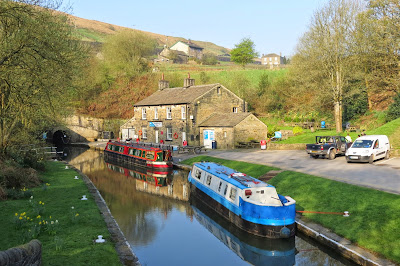 Two narrowboats moored by the stone arch of the tunnel entrance. A stone building stands to the right of the tunnel with hills and other buildings behind.