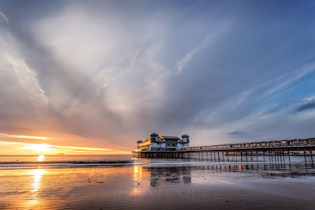 Sunset light reflects on the wet sand at the Grand Pier in Weston-Super-Mare