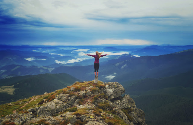 Woman standing on top of a mountain with outstretched arms
