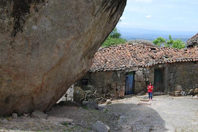 Una niña y una de las casitas de Monsanto junto a una de las enormes piedras. Se aprecia perfectamente el tamaño de esta.
