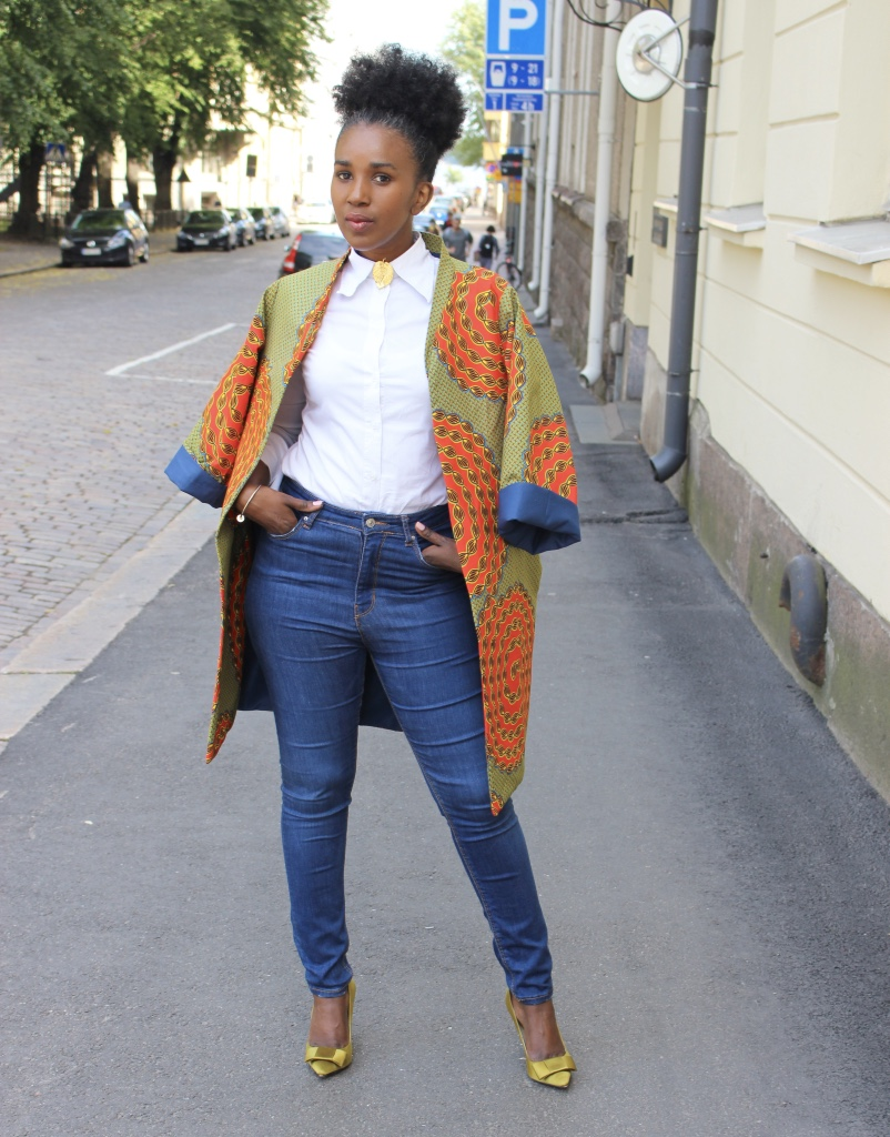lady in an African print coat styled with a white shirt and denim jeans