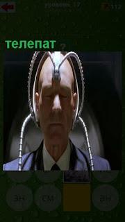 сидит мужчина в костюме телепат и на голове закреплены провода