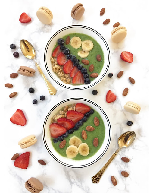 Green smoothie with granola, strawberries, blueberries, and almonds